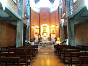 L'immagine mostra l'interno del Santuario di Nettuno dedicato a Santa Maria Goretti, con la navata centrale e l'altare maggiore.
